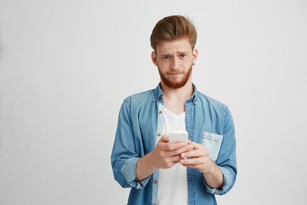 カメラ目線のスマートフォンを保持しているひげの失望した動揺の若い男。