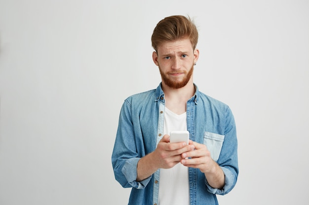 Dissapointed upset young man with beard holding smart phone looking at camera.
