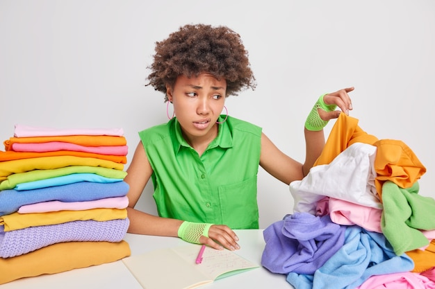 Dissatisfied african american woman picks dirty clothes from pile works in laundry makes notes in notebook poses against white wall feels aversion has disgusting face. big laundering concept