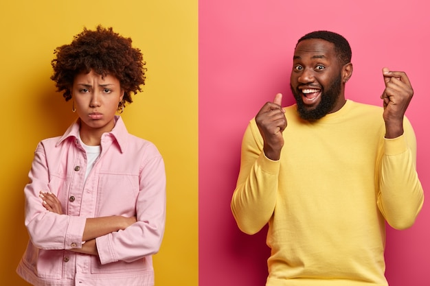 Dissatisfied african american woman stands with arms folded, displeased after quarrel with husband, triumphing dark skinned man raises both arms. ethnic couple stand over two colored wall