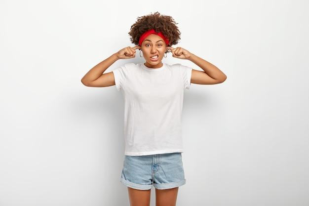 Donna afroamericana insoddisfatta incapace di concentrarsi, disturbata da un forte rumore, tappi le orecchie con le dita, aggrotta le sopracciglia e sembra infastidita, indossa abiti casual, isolato su bianco