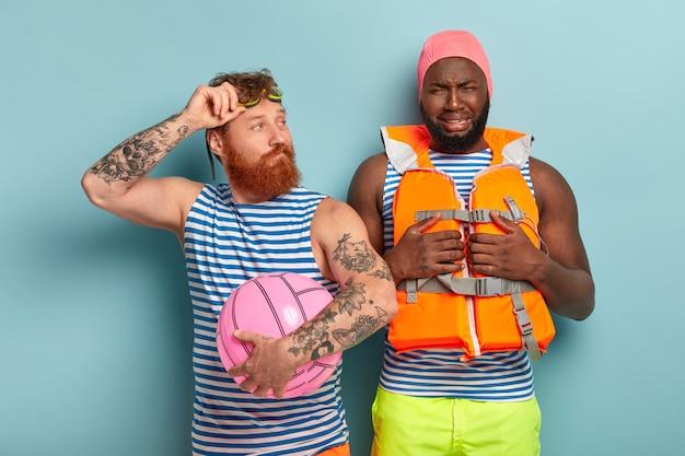 불만족스러운 아프리카 남자가 정신이 낮고 수영 모자와 구명 조끼를 착용합니다.