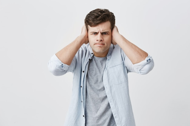 Dissatisfied and angry young caucasian male dressed in light blue shirt, frowning his face, closing ears with palms, annoyed and tired of noise, refusing to listen to someone`s words. body language