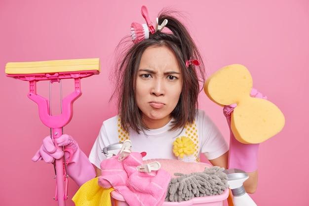 불만족 된 성가신 젊은 아시아 여성이 불만을 품은 표정으로 얼굴을 찌푸린 얼굴은 걸레와 스폰지가 부담없이 옷을 입고 분홍색 벽 위에 고립 된 청소 장비와 세제를 사용합니다.