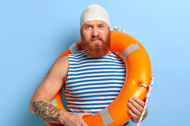 Dissatisfied bearded ginger man looks angrily, wears rubber white swimcap, carries lifering, expresses negative emotions