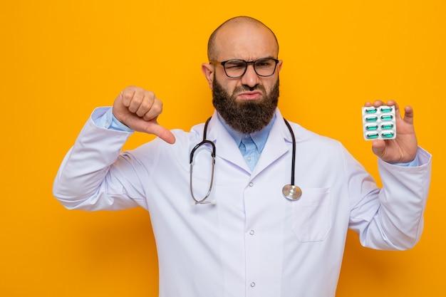 首の周りに聴診器を備えた白衣を着た不満のひげを生やした男性医師は、錠剤で水ぶくれを保持している眼鏡をかけています