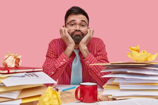 Dissatisfied bearded man keeps hands under chin, looks through spectacles with apathy, wears formal clothes, surrounded with stack of papers