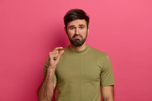 L'uomo barbuto insoddisfatto fa un piccolo gesto, mostra qualcosa di minuscolo con le dita