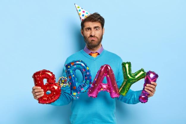 不満の誕生日の男はカラフルな文字の形の風船を持っています