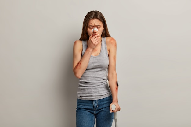 Dissatisfied bruised woman with various hematomes, faces traumatic experience