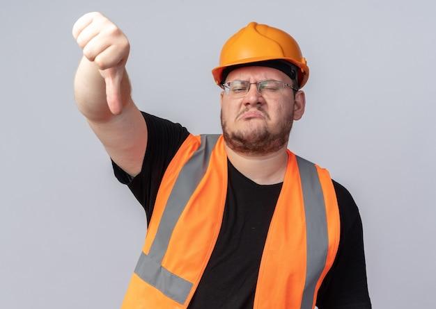 Uomo costruttore insoddisfatto in giubbotto da costruzione e casco di sicurezza guardando la telecamera con il viso accigliato che mostra il pollice verso il basso in piedi su sfondo bianco