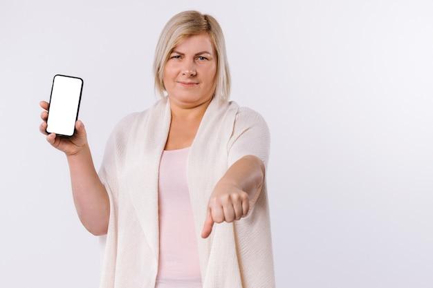 不満のある白人女性が電話スクリーンを見せている一方で、嫌いなサインを見せています。白い背景に親指を下に向けます。高品質の写真