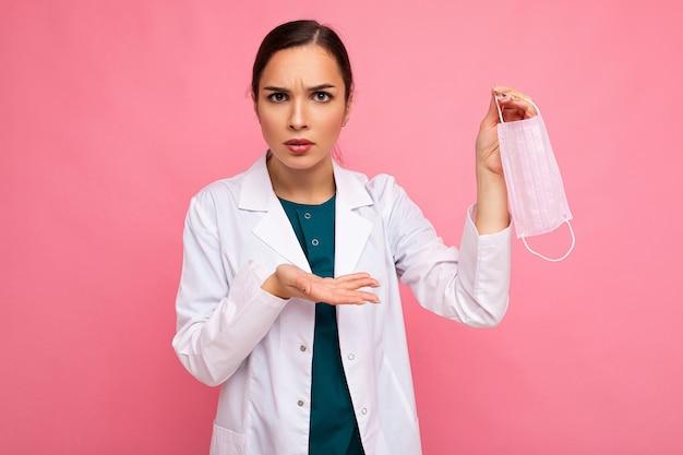 ピンクの壁のコロナウイルスで分離された保護フェイスマスクを示す不満の白人女性または