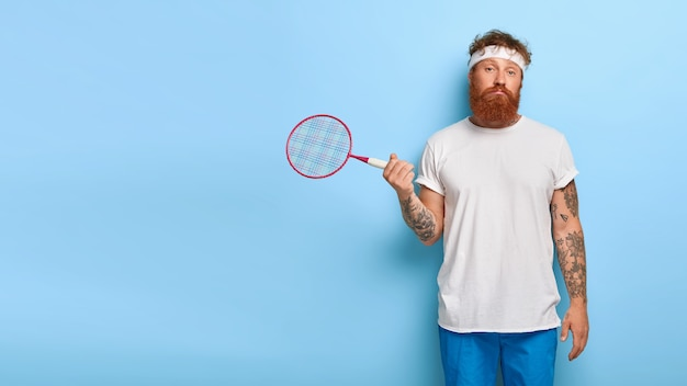 Il ragazzo attivo insoddisfatto e incapace posa con la racchetta da tennis, fa sport per mantenersi in salute