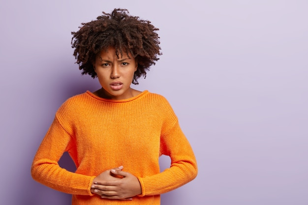 Dissatisfied dark skinned female keeps hands on stomach, suffers from pain, has menstruation, wears orange jumper, has curly hair, isolated over purple wall, free space for your advertising