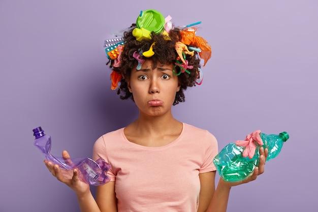 La donna insoddisfatta dalla pelle scura si preoccupa dell'ambiente pulito, tiene in mano due bottiglie di plastica accartocciate, raccoglie la spazzatura ovunque, è triste a causa dei problemi di inquinamento della natura, si preoccupa dell'ecologia