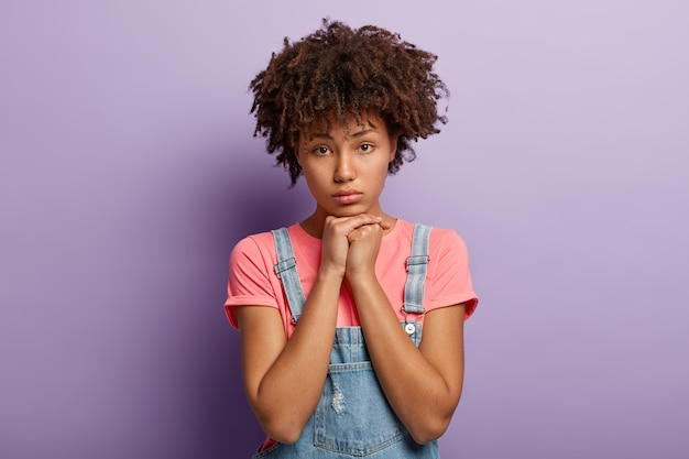 Dissatisfied dark skinned woman with curly hair, holds hands under chin, feels lonely and dejected after quarrel with boyfriend, has afro hairstyle, wears casual t shirt isolated on purple