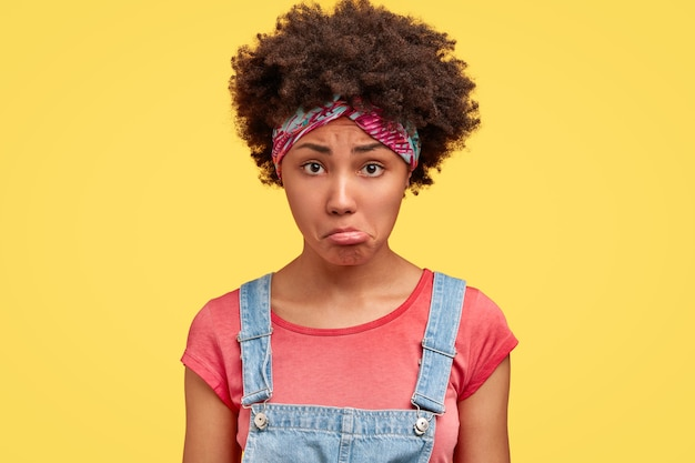 La giovane donna dalla pelle scura insoddisfatta porta il labbro inferiore, viene maltrattata da qualcosa di spiacevole, ha un'espressione infelice, indossa una maglietta rosa e una salopette di jeans, si trova al coperto contro il muro giallo