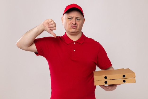 白い背景の上に立っているピザボックスを保持している親指を下に示しているカメラを見て赤い制服とキャップの不満の配達人