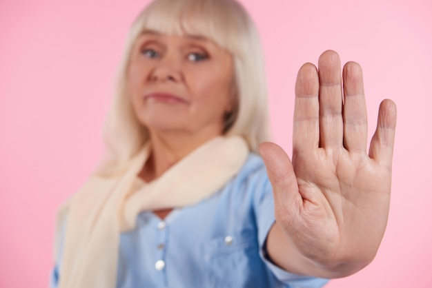 Dissatisfied elderly woman shows stop sign.
