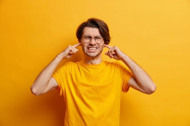 Insoddisfatto uomo europeo stringe i denti non riesce a concentrarsi a causa del rumore indossa occhiali maglietta casual sente urlo straziante isolato sul muro giallo. non volendo ascoltare