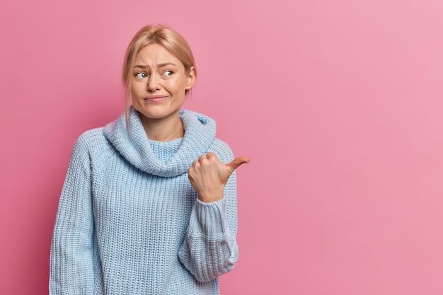 Недовольная европейская женщина показывает пальцем на место для копирования, испытывает плохие чувства, хмурится, носит повседневный джемпер