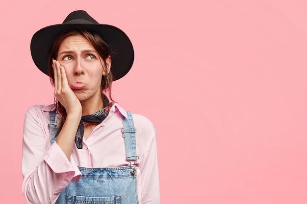不満を持った女性農業労働者が頬に手をかざし、必死に上向きに見え、唇をすぼめ、不満の表情を持ち、ピンクの壁に立ち向かう