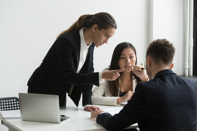 Dissatisfied female executive blaming threatening male employee at team meeting
