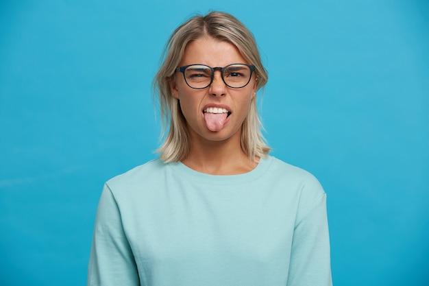 不満な女性モデルは顔をしかめ、嫌な表情をしている