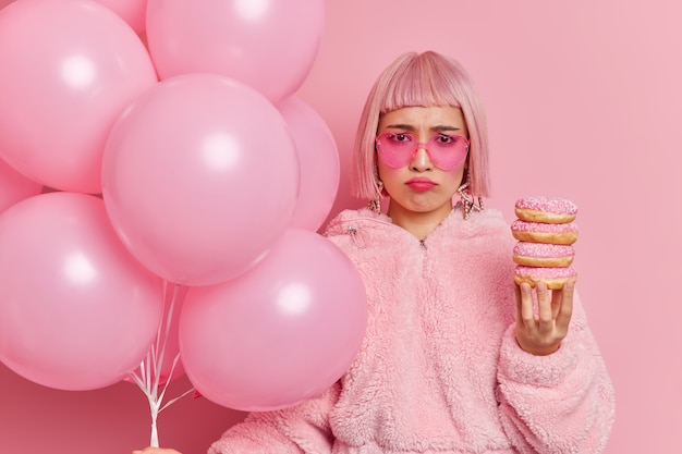 Dissatisfied frustated asian woman wears trendy sunglasses has bad mood as celebrates birthday alone holds pile of doughnuts and inflated balloons