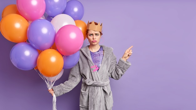 Dissatisfied frustrated birthday girl has sad face expression being tired of organizing holiday holds bunch of multicolored inflated balloons