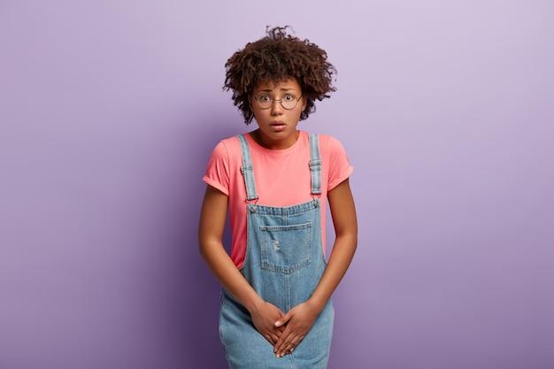 La ragazza insoddisfatta tiene le mani sull'inguine, preme il basso addome, ha un forte bisogno di servizi igienici, ha la sindrome della cistite
