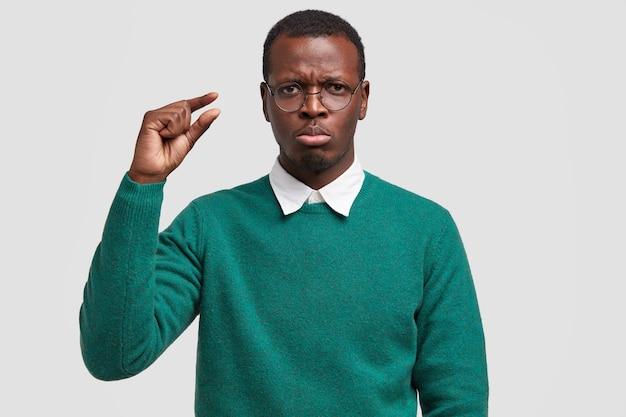 Недовольный мрачный темнокожий мужчина жестикулирует в помещении, показывает что-то маленькое, поджимает губы, демонстрирует размер, носит зеленый свитер, хмурится