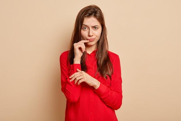La bella donna insoddisfatta solleva le sopracciglia, stringe le labbra, guarda con rabbia, tiene la mano vicino alla bocca, indossa una camicia rossa elegante, si erge sul muro beige, scontenta per il suggerimento di qualcuno