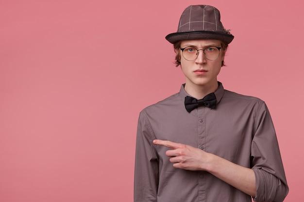 Недовольный сварливый неудовлетворенный хмурый элегантно одетый молодой стройный парень изолирован на розовом, указывая указательным пальцем влево на копировальной площади