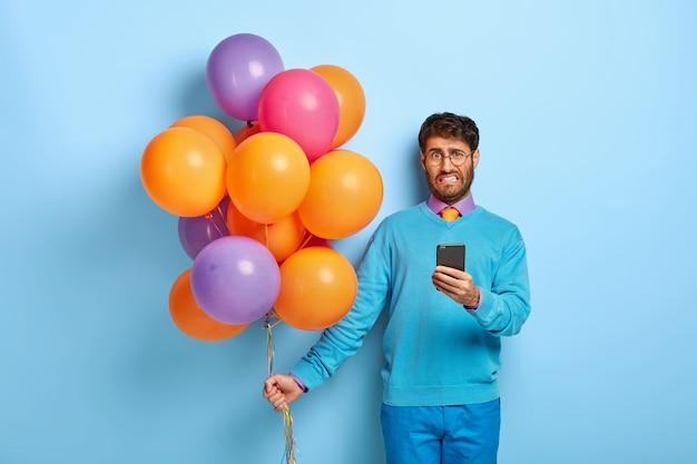 Недовольный парень с воздушными шарами позирует в синем свитере
