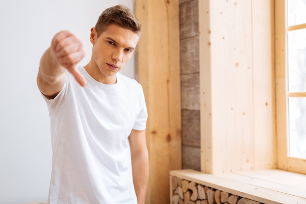Dissatisfied. handsome discontent well-built adolescent being determined and wearing casual clothes and showing his thumb down
