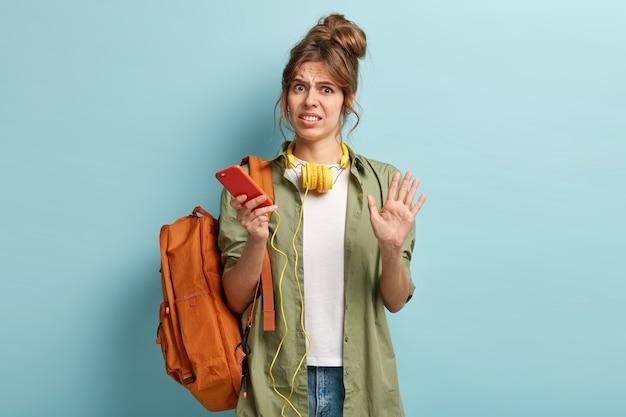 La ragazza hipster insoddisfatta fa il gesto di arresto con dispiacere, ascolta la musica tramite il moderno telefono cellulare e le cuffie stereo