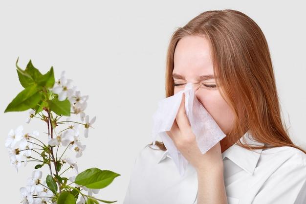 不快な病気の若い女性がティッシュでくしゃみをし、顔をしかめ、鼻を走らせ、花の枝の近くでポーズし、エレガントなシャツを着ている