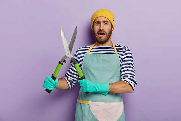 Dissatisfied landscpae designer or gardener holds gardening shears, going to cut green bush, wears yellow hat
