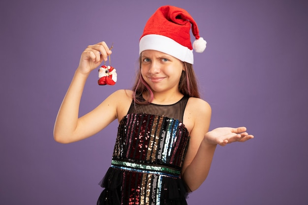 Dissatisfied little girl in glitter party dress and santa hat holding christmas toys looking at camera raising hand in displeasure and indignation standing over purple background