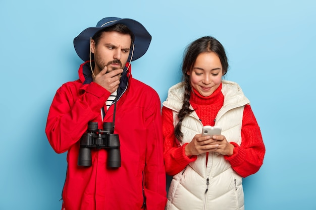 Dissatisfied man holds chin, looks angrily at smartphone of girlfriend, dressed in casual wear, carries binoculars and happy asian girl types message, focused at cellular
