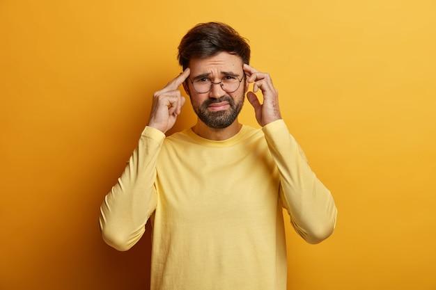 不満のある男は、人差し指で寺院に触れ、顔を笑い、耐え難い頭痛に苦しみ、カジュアルなセーターを着て、屋内で圧力と苦痛を感じ、黄色で隔離され、激しく考えます