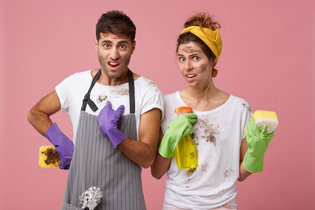 Dissatisfied man and woman in dirty clothes holding sponge and washing spray being untidy
