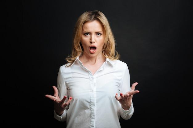불만족스러운 성숙한 분노한 여자가 짜증을 표현하고 고함을 지르며 미친 듯이 몸짓을하고 검은 벽에 고립 된 상태로 서 있습니다.