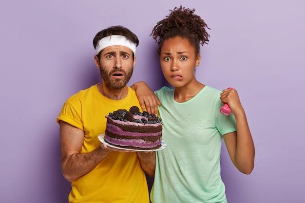 Недовольные женщина и мужчина смешанной расы пытаются вести здоровый образ жизни, носить спортивную одежду