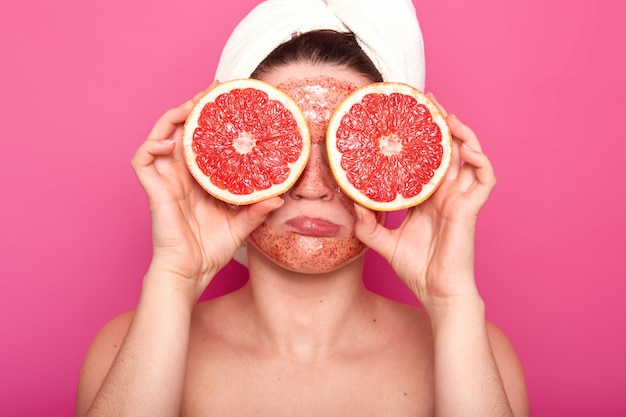 Dissatisfied naked woman frowns her face holding parts of rape grapefruit in both hands