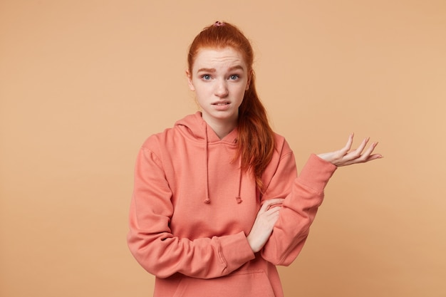 Dissatisfied red-haired woman with a tail dressed in hoodie with someone arguing one hand raised palm up trying to prove something