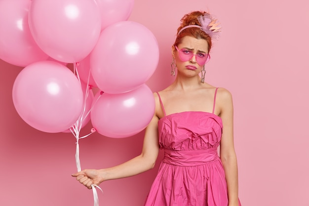 Dissatisfied redhead woman looks sadly  wears festive dress holds bunch of balloons feels unhappy and lonely on birthday party isolated over pink wall sad about getting older.