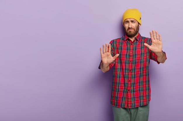 不満の悲しい男は拒否の兆候を示し、手のひらを伸ばしたままにし、私を安心させてくださいと言い、黄色い帽子と市松模様のシャツを着て、嫌な表情をしています